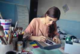 artist at work at her desk, painting.
