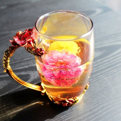 Steaming mug of tea with blossom inside, for tea helps artists post