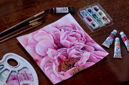 watercolor of pink flower with paints and brushes on desk for art newsletter post