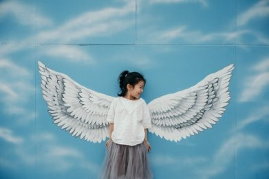 child with angel wings behind her from art mural, for email signature post