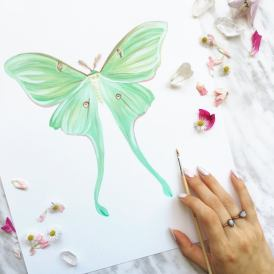 Luna moth in a flat lay photo with artist's hand and paintbrush
