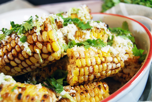 Spicy Ancho Grilled Corn with Avocado Crema and Cotija: Delicious grilled corn gets kicked up a notch with spicy ancho chili. Then it's paired with a cooling avocado crema and salty cotija cheese!