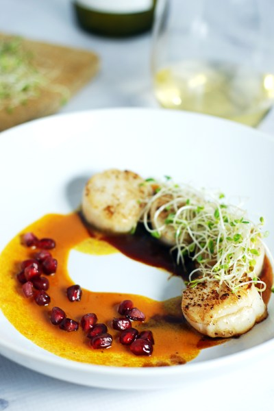 Seared Scallops with Duo of Pomegranate and Carrot Sauce: Delicious seared scallops are paired with a duo of pomegranate and carrot sauces in this simple yet elegant dish.