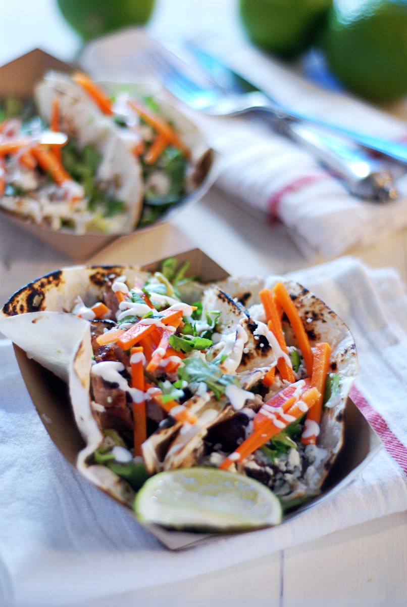 These crispy pork belly tacos feature quick pickled carrots, smashed avocado, fresh homemade crema, and queso fresco.