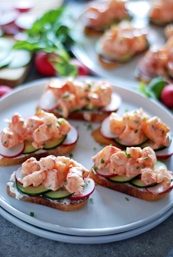 These adorable shrimp toasts feature creamy shrimp salad, fresh cucumbers and radishes, and cream cheese all atop a crunchy baguette.