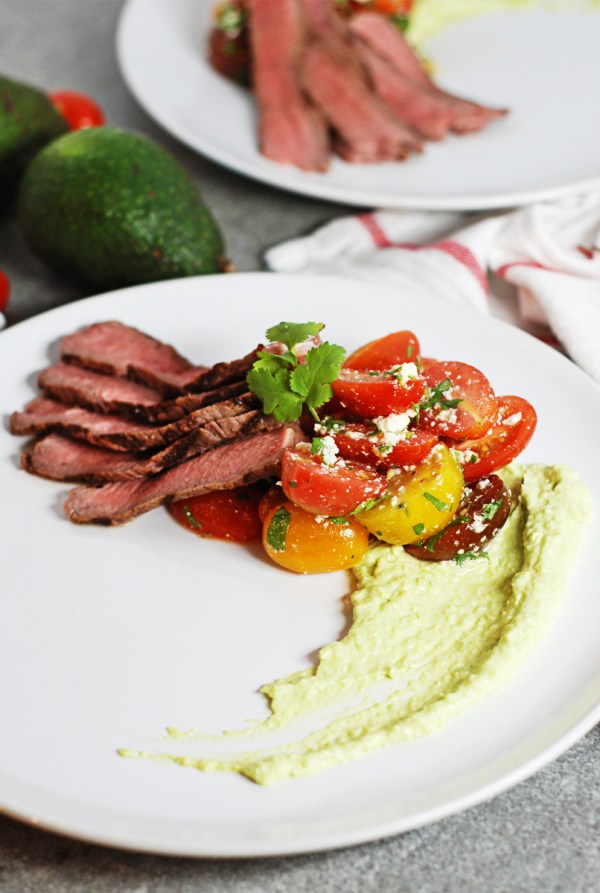 These perfect grilled steaks are paired with a refreshing and light cherry tomato salad and a cool avocado crema - the perfect summertime meal!