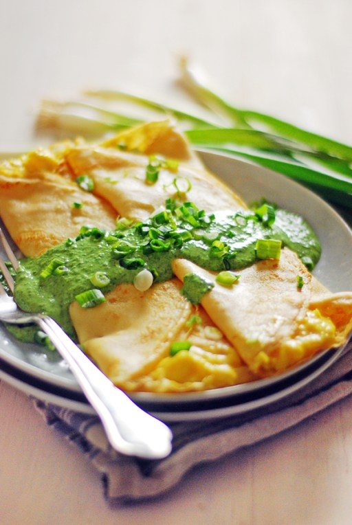 These savory breakfast crepes feature scrambled eggs and white cheddar cheese, and are topped with a creamy spinach sauce and fresh green onions.