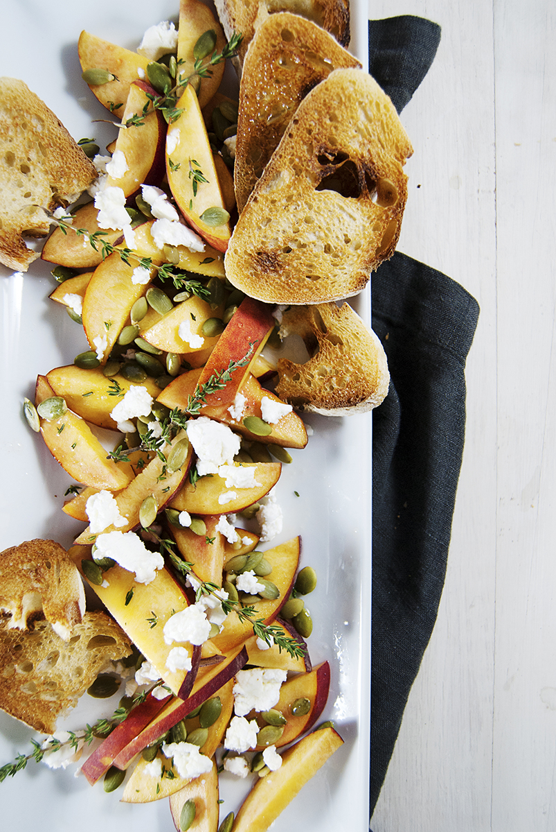 This fresh peach salad is the perfect simple side salad for your spring and summer meals! It features fresh peach slices, toasted pepitas, creamy goat cheese, and crostini with a lemon honey drizzle.