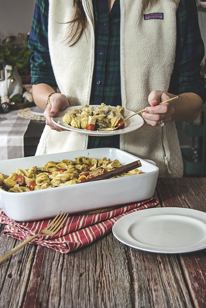 Pesto macaroni and cheese is what you need in your life! A creamy white cheddar base with pesto, chicken, orecchiette, cherry tomatoes, and mushrooms.