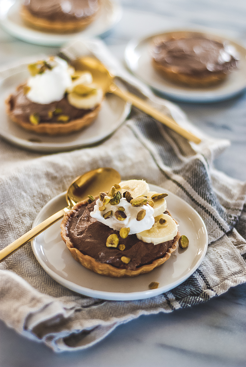 These chocolate cardamom tarts feature a rich chocolate custard base infused with toasted cardamom, fresh bananas, toasted pistachios and homemade whipped cream all in a miniature size!