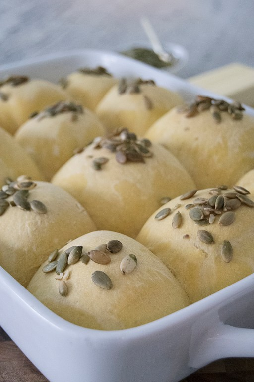 These simple pumpkin dinner rolls are the perfect accompaniment to any winter or fall meal, and are topped with toasted pepitas!