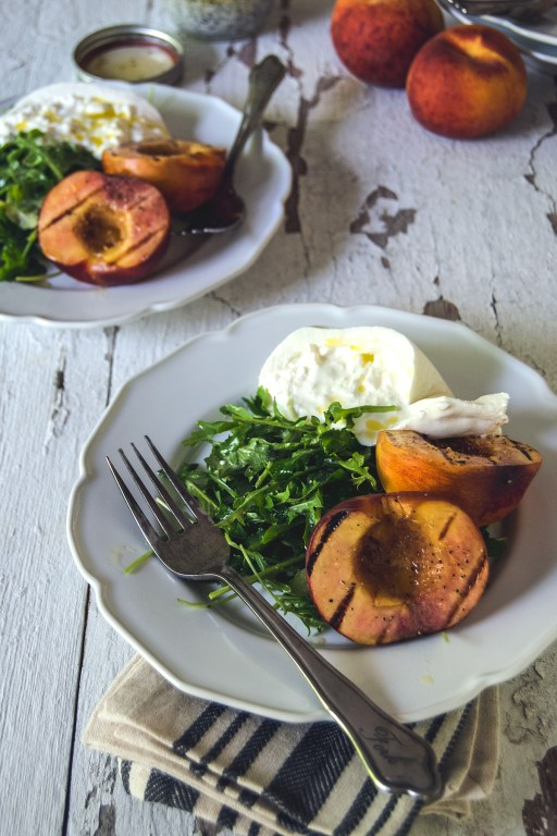 Celebrate the summer with this simple grilled peach and arugula salad, featuring fresh burrata and a simple creamy poppy seed dressing.