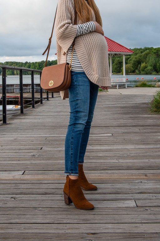 Stay cozy this Labor Day weekend with this insanely comfortable beige tunic sweater, paired with stripes, skinny jeans, and suede booties!