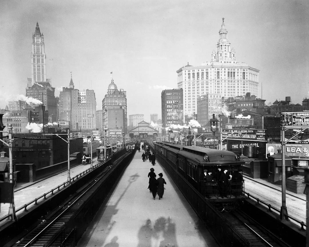 Pedestrians crossing the Brooklyn Bridge next to a railcar, early 1900s