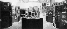Interior to Mel'nikov's Soviet Pavilion in Paris, 1925. The central podium features a model of I. Rabinovich's set for the 1923 production of Lysistrata. Further behind are some of Varvara Stepanova's costrumes for Meierkhol'd's 1922 production of Tarelkin's Death. Finally, Aleksandr Vesnin's set design for Tarov's 1923 version of GK Chesterton's Man Who Was Thursday.