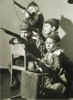 Margaret Bourke-White, Russian kindergarten boys clad in miniature caps w. red stars, aiming toy rifles, barricaded behind classroom furniture, while playing war game (Moscow, August 1941)