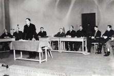 Hendrik de Man als spreker aan een tafel met achter hem het bureau met o.a. vlnr.- ?, Isidore Delvigne, Léon-Eli Troclet, ?, Jules Merlot, ?, ?, ?. Luik, jaren 1930