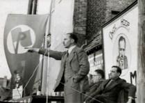 Hendrik de Man als spreker tijdens een meeting voor het Plan van de Arbeid. Rechts zittend- Edward Anseele jr. Jaren 1930