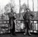 Zwart-witfoto van Hendrik de Man (links) en een andere man met pijp en klompen tonen de visvangst. Jaren 1940