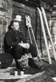 Zwart-witfoto van Hendrik de Man met pijp rustend voor een hut na het skien. Haute Savoie, Frankrijk, 8 februari 1928