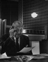 the-architect-mies-van-der-rohe-wearing-glasses-sitting-looking-at-a-paper-with-model-of-new-ibm-building-in-background-chicago-il-ca-1960s-photo-by-hedrich-blessing