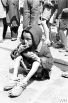 A destitute Jewish child eating a piece of bread in the street of the ghetto