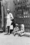 An emaciated mother with her twin daughters in the ghetto