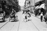 Crowds of pedestrians and street rickshaws in busy Karmelicka Street in the ghetto