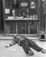 Dead man lies in front of a shop in the Warsaw ghetto