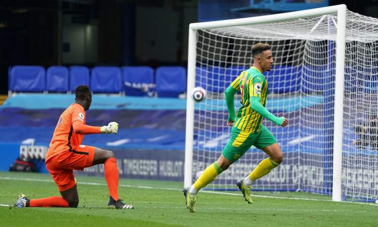 LONDON, ENGLAND - APRIL 03: Callum Robinson of West Bromwich Albion scores their side's fifth goal over Edouard Mendy of Chelsea during the Premier League match between Chelsea and West Bromwich Albion at Stamford Bridge on April 03, 2021 in London, England. Sporting stadiums around the UK remain under strict restrictions due to the Coronavirus Pandemic as Government social distancing laws prohibit fans inside venues resulting in games being played behind closed doors. (Photo by John Walton - Pool/Getty Images)