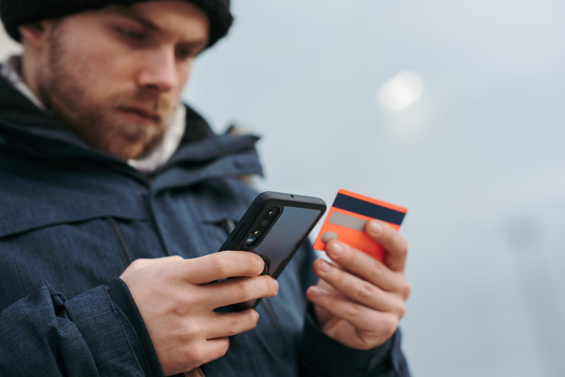 serious man paying online purchases using smartphone on street