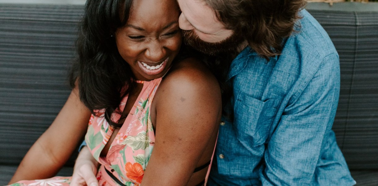 couple snuggling and smiling, man kisses woman's cheek