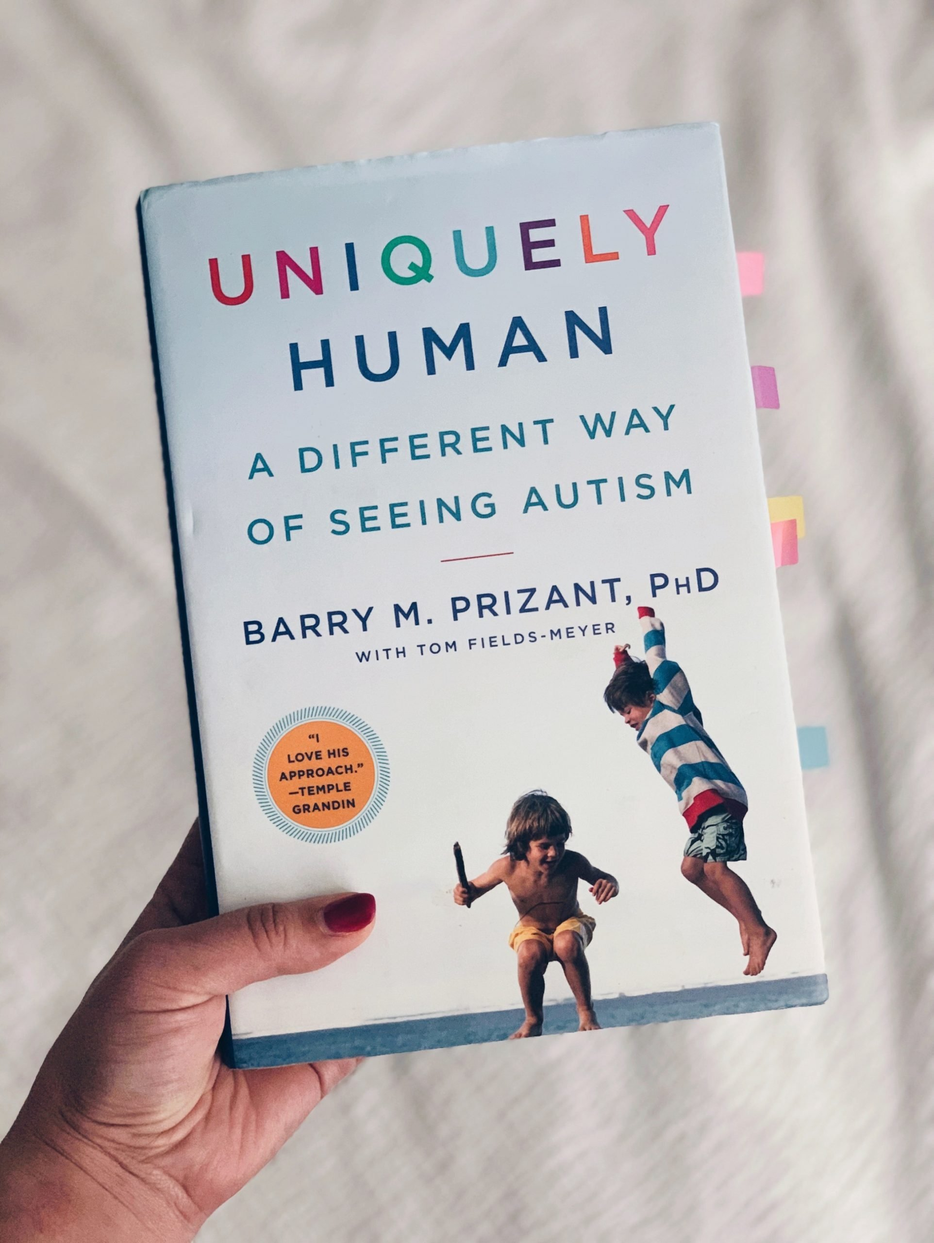 Hand holding book, Uniquely Human - Barry M. Prizant, PhD
