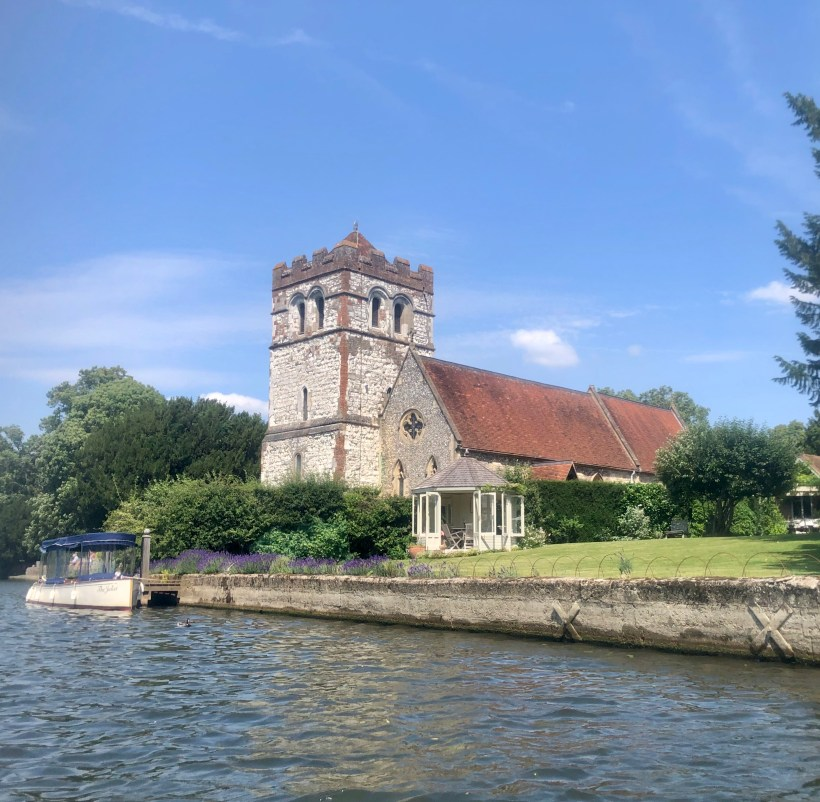All Saints Bisham with its 12th century tower alongside the river thames and pleasure boat
