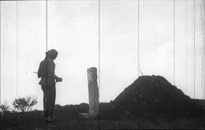 Xiao Yu stands at her father's grave.
