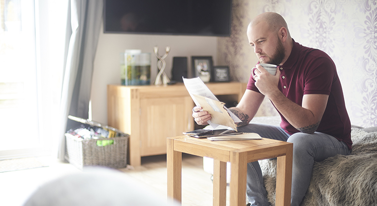 Home owner reading paperwork sat on the sofa in his living room