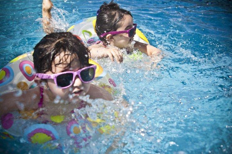 2 girls in pool floating in tubes