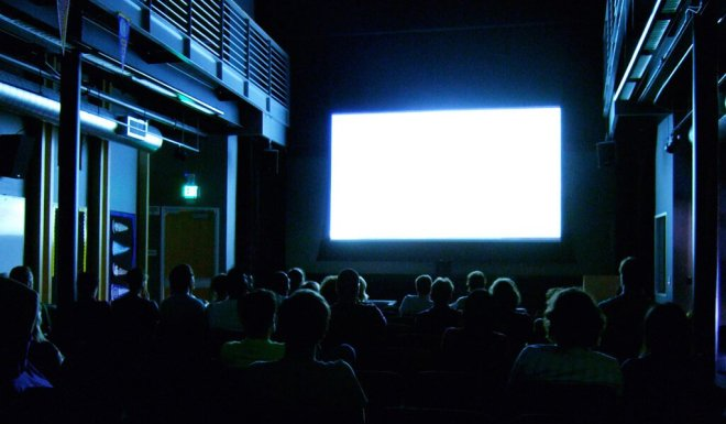 People sitting in front of a empty movie screen