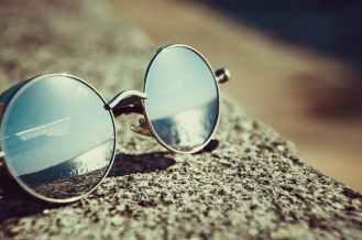 silver framed hippie sunglasses on concrete