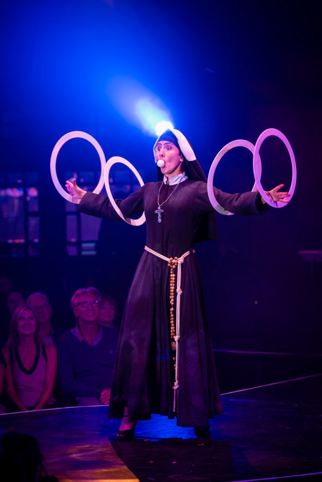 A nun stood on a stage, her arms out straight to either side with 2 white juggling rings on each arm and a ping pong ball in her mouth