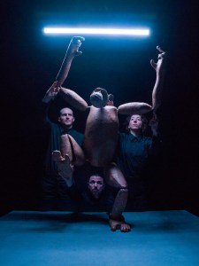 Photo of a life-sized chimp puppet standing on a blue table, reaching its arms up towards a blue neon strip light above its head. The three puppeteers are in the shadows behind, eyes focused on the puppet. Two stand at either side, holding the puppet's elbows. The other man is low in the centre, holding the puppet's feet at either side of him. One of the puppet's legs is raised as if climbing a ladder.