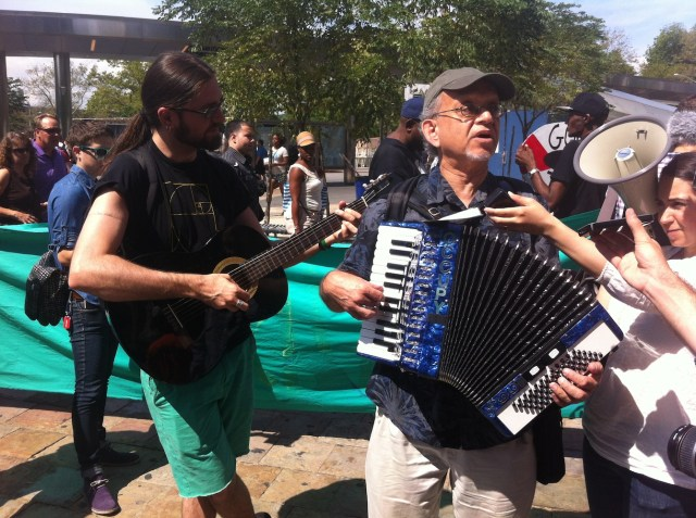 Two-man guitar and accordion band lead group in song before embarking on march