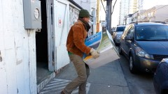 Gibbs carries box of off-grid solar equipment to bring to Roca's studio