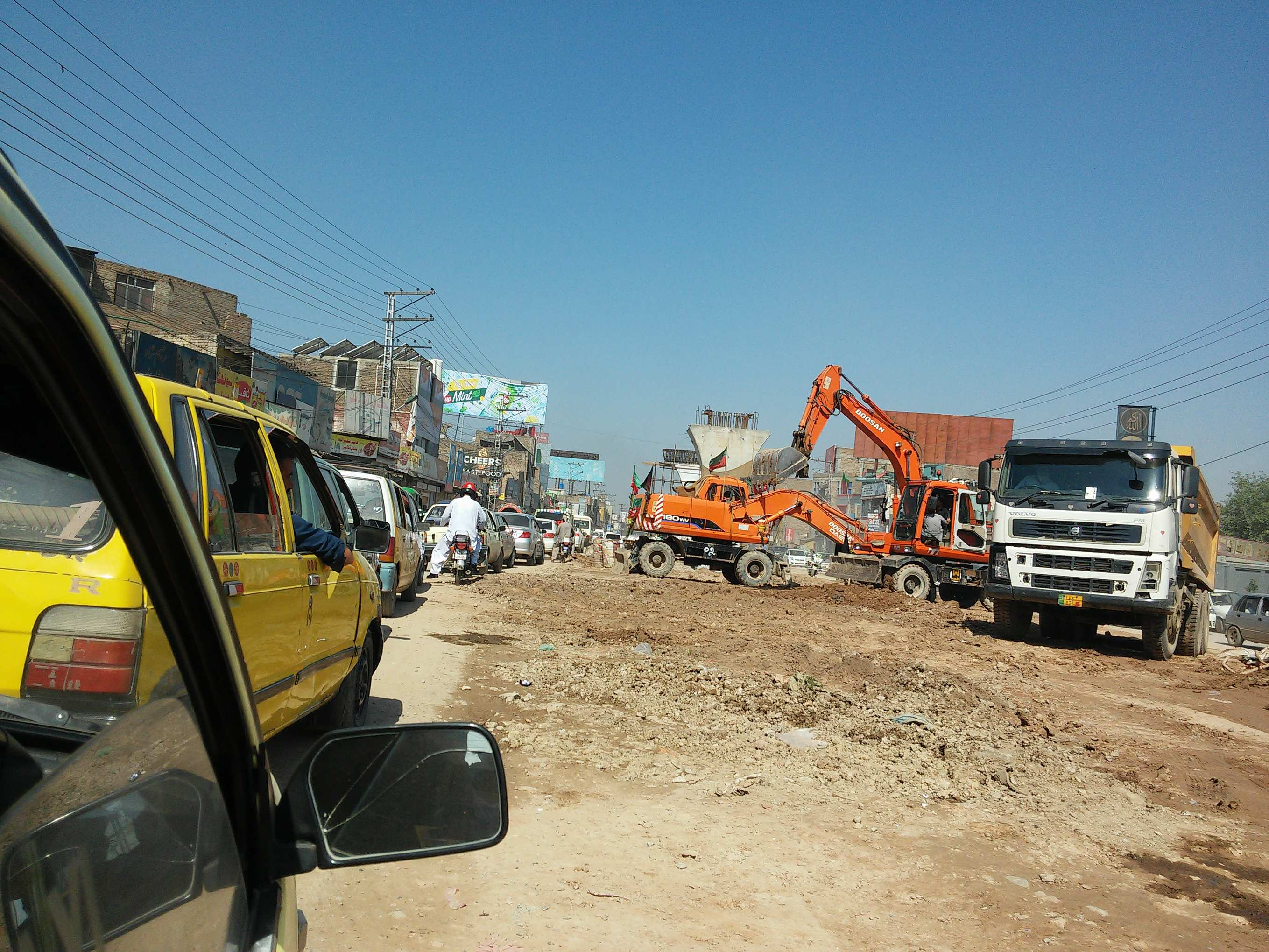 Cars in stand still traffic with nothing to seperate them from the construction site of BRT less than a meter away