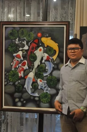 """Mario Villanueva with his artwork entitled """"Koi"""", one of the pieces on display at the ongoing 13 Ubay Filipino Casual Dining exhibit"""