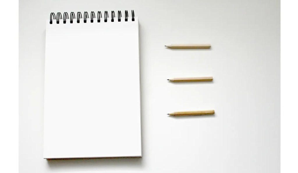 decorative image: notepad and pencils