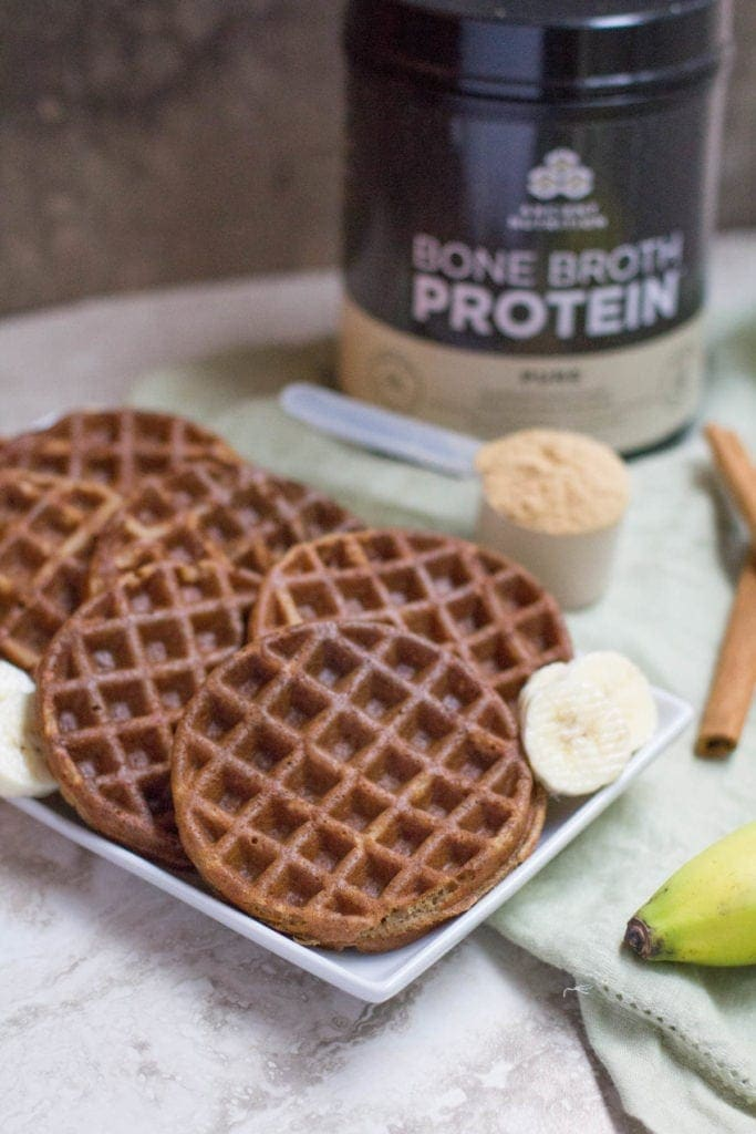 A plate of crispy Healthy Blender Banana Bread Protein Waffles with bananas, cinnamon sticks & protein powder to the side