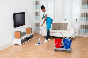 Young Woman Cleaning Floor With Mop In Living Room