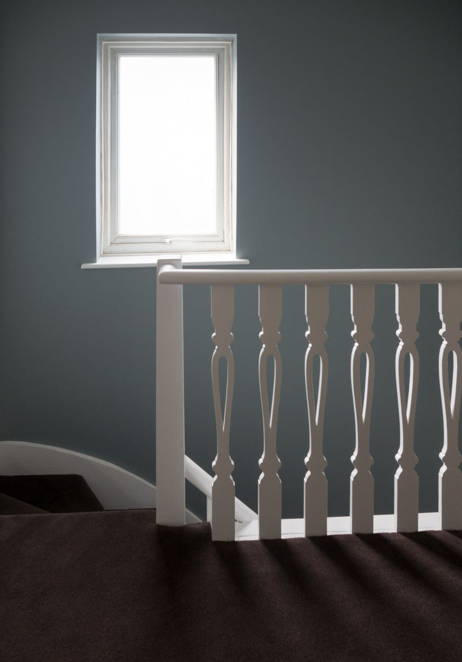 photo of white window frame an white wooden stair balustrade