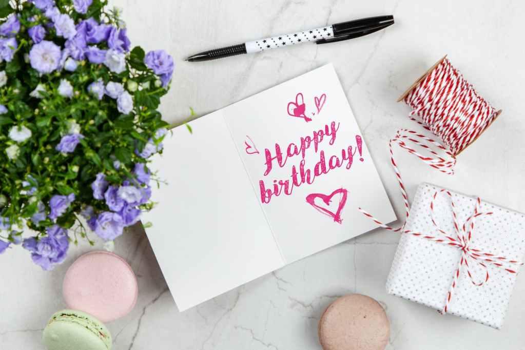happy birthday card beside flower thread box and macaroons